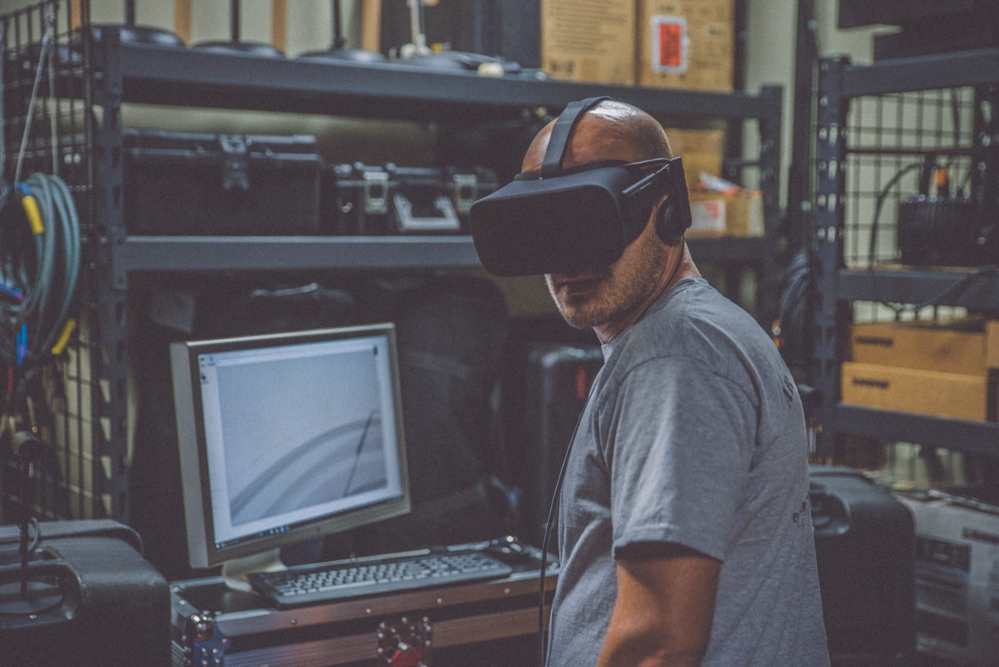 person using black VR Headset in front of computer